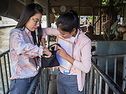19 JANUARY 2015 - BANGKOK, THAILAND: Women look for the 2 Baht ( about .06¢ US) fare in their purses after riding across the Khlong (canal) and the ferry to the Sukhumvit side of Khlong Saen Saeb. The small ferry crosses Khlong Saen Saeb throughout the day. It is powered by an diesel engine that uses a system of cables to pull the ferry the 30 feet across the canal. It's used by pedestrians  who need to get across the khlong. The nearest bridge is about ½ mile away.     PHOTO BY JACK KURTZ