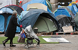 © Licensed to London News Pictures. 13/02/2012. London, UK. A woman pushes a pram past tents at the Occupy London camp at St Paul's Cathedral on February 13th, 2012 in London, England. An appeal is being heard at the High Court today (13/02/2012) against a judgement handed down  for the group's eviction from the protest camp brought by the City of London Corporation. Photo credit : Ben Cawthra/LNP