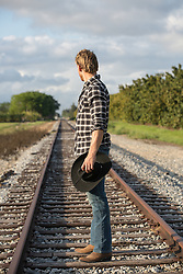 cowboy standing on railroad tracks looking off