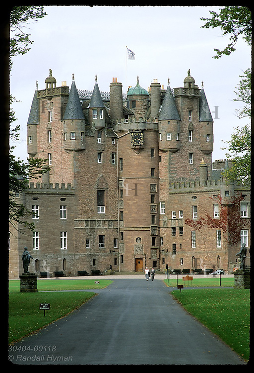 Two women walk path in front of Glamis Castle, childhood home of the Queen Mother;  Glamis, Angus, Scotland.