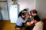 (MODEL RELEASED IMAGE). Because Oyuntsetseg (Oyuna) Lhakamsuren is working at her pharmacy tonight, her son Batbileg walks the meal over to her and then the two of them sit down with Oyuna's husband, Regzen Batsuuri, and a niece, to eat their dinner. Hungry Planet: What the World Eats (p. 233). The Batsuuri family of Ulaanbaatar, Mongolia, is one of the thirty families featured, with a weeks' worth of food, in the book Hungry Planet: What the World Eats.