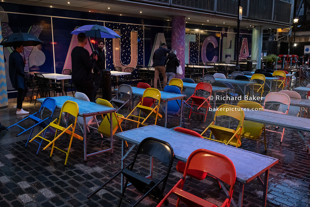 On a rainy night in Soho, tables set up for social distancing on Berwick Street remain vacant at a time when recently re-opened bars and restaurants are desperate for customer business during the coronavirus pandemic, on 27th August 2020, in London, England.