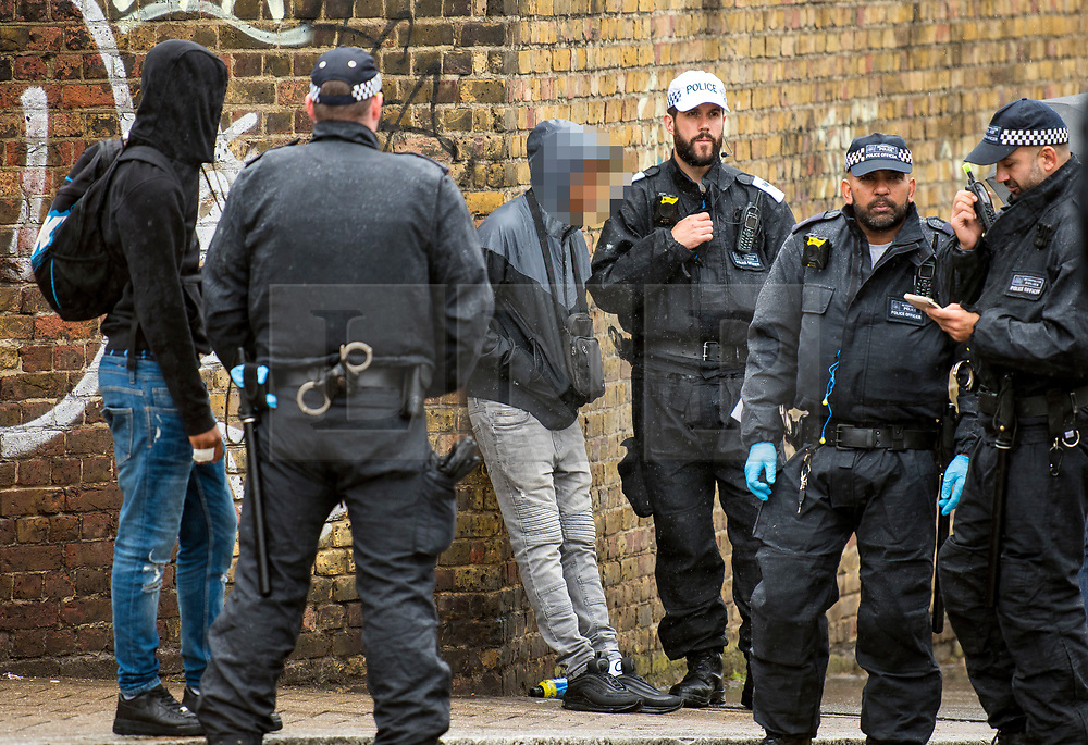 © Licensed to London News Pictures. 26/08/2018. London, UK. A young man is questioned by police at family day of the 2018 Notting Hill Carnival. Up to 1 million people are expected to attend this weekend's event that is one of the worlds largest street festivals. Photo credit: Ben Cawthra/LNP