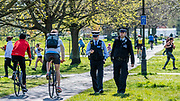 Police patrol Clapham Common and gently make people aware of the need for social distancing and that they are only supposed to be out for exercise - A sunny day and people are out in reasonable numbers, throughout London, to get their daily exercise.  The 'lockdown' continues for the Coronavirus (Covid 19) outbreak in London.