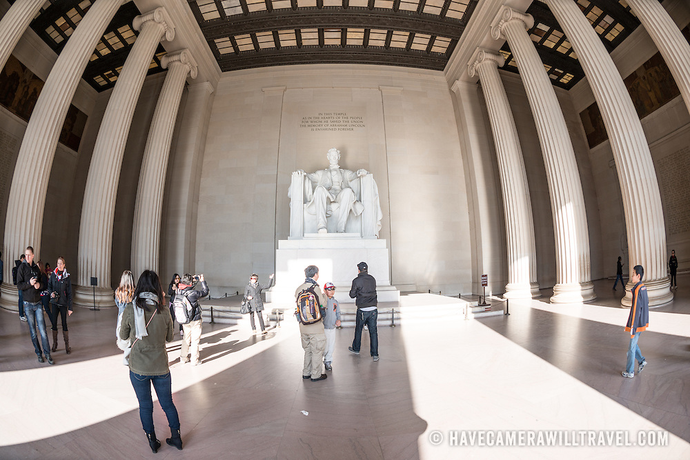Tourists visit the statue of Abraham Lincoln at the Lincoln Memorial in Washington DC. Wide-angle fisheye lens.