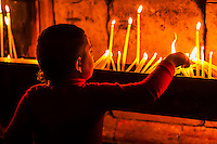 Boy lighting candles, Church of the Holy Sepulchre (site of the last five stations of the Cross and venerated as the place where Jesus was crucified and buried), the Christian Quarter, Old City, Jerusalem, Israel.