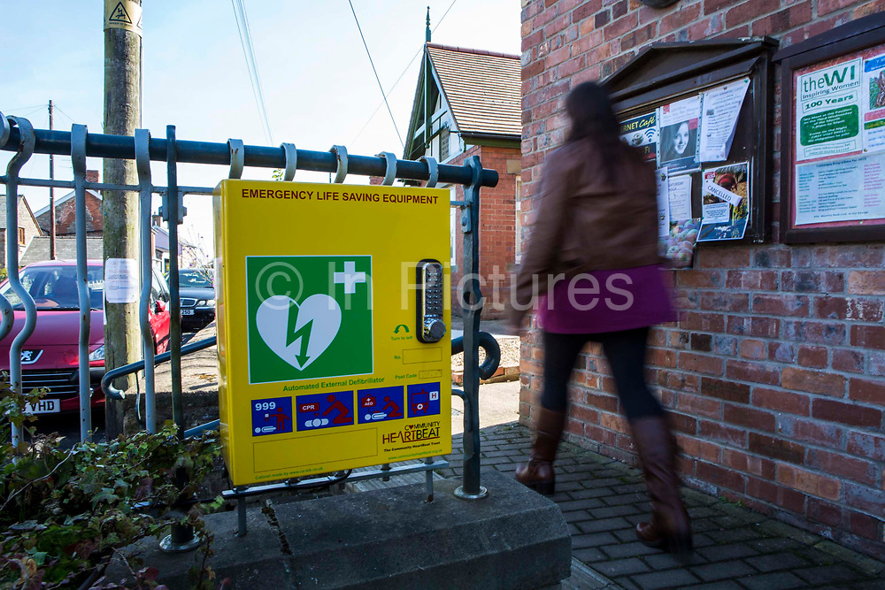 A defibrillator supplied with money from the community wind turbine project outside Lydney village hall. A community energy project organised by the Resilience centre, Forest of Dean. Gloucestershire.