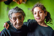 "Portrait of Maria (85) - the oldest inhabitant of the Roma settlement ""Budulovska Street"" with 11 years old Celestina. ""Budulovska Street"" is a segregated Roma settlement located about 2,5 km behind the city of Moldava nad Bodvou close to Kosice in east Slovakia. The city has roughly 11200 inhabitants, about 1980 (18%) of them have Roma ethnicity and around 800 are living at the segregated settlement 'Budulovska Street' (2014)."