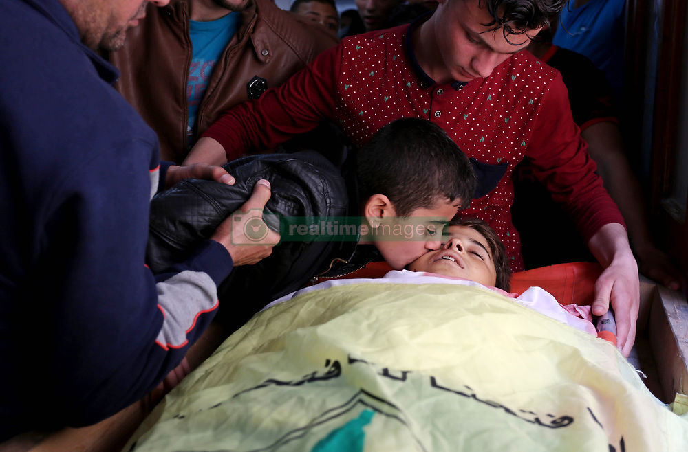 April 28, 2018 - Khan Yunis, Gaza Strip - Relatives of 15-year-old Palestinian teenager Azzam Oweida, who died of his injuries sustained by Israeli security forces during clashes at the Israel-Gaza border, mourn over his body during his funeral in Khan Yunis in the southern Gaza Strip.  (Credit Image: © Ashraf Amra/APA Images via ZUMA Wire)