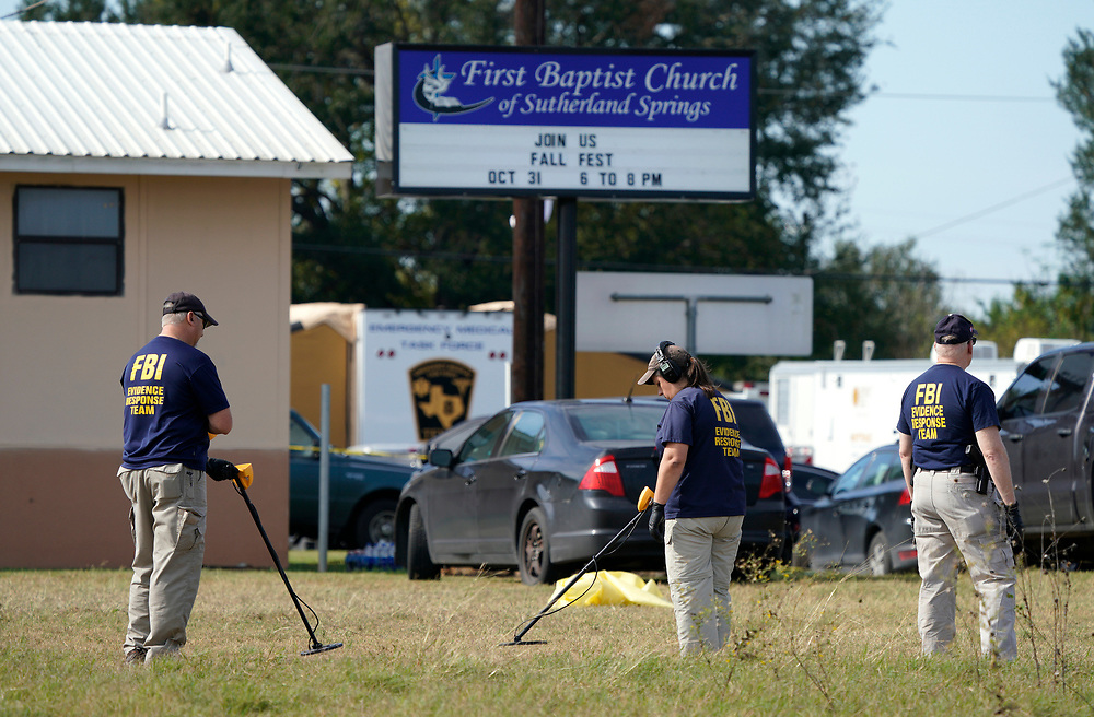 Members of the FBI Evidence Response Team use metal detectors  outside the site of the shooting at the First Baptist Church of Sutherland, Texas, U.S., November 6, 2017.  REUTERS/Rick Wilking