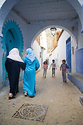 Two veiled women walk arm in arm past three children playing in the street under an archway in Chefchaouen medina, Morocco.