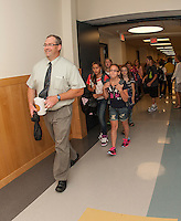 Laconia Middle School Principal Eric Johnson leads his sixth grade students to their wing as they begin their first day of classes Tuesday morning.  (Karen Bobotas/for the Laconia Daily Sun)