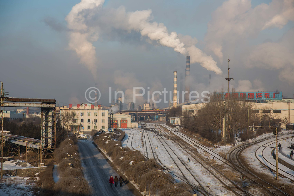 Employees walk past train tracks as water vapor and smoke rise from a Tonghua Iron & Steel Group Co. plant in the distance in the Erdaojiang district in Tonghua, Jilin province, China, on Wednesday, Jan. 6, 2016. The citys once-vaunted state-run steel mills have slipped inexorably into decline, weighed down by slumping global markets, a changing economy, and the burden of costs and responsibilities to the people of the town they fostered. Previous attempts to privatise the enterprise have met with stiff resistance, one such attempt resulted the mob lynching and death of a private businessman who wanted to invest and streamline the operation.