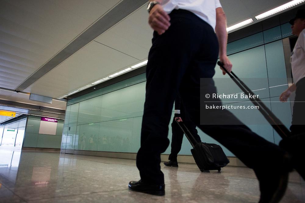 Arriving British Airways flight deck and cabin crew stride through arrivals after long-haul flight to Heathrow Airport's T5
