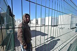 © Licensed to London News Pictures . 04/03/16 . A young Kurdish man stands next to new container living quarters in the Calais Jungle, France. French authorities are continuing to clear parts of the migrant camp.  Photo credit : Ian Homer/LNP