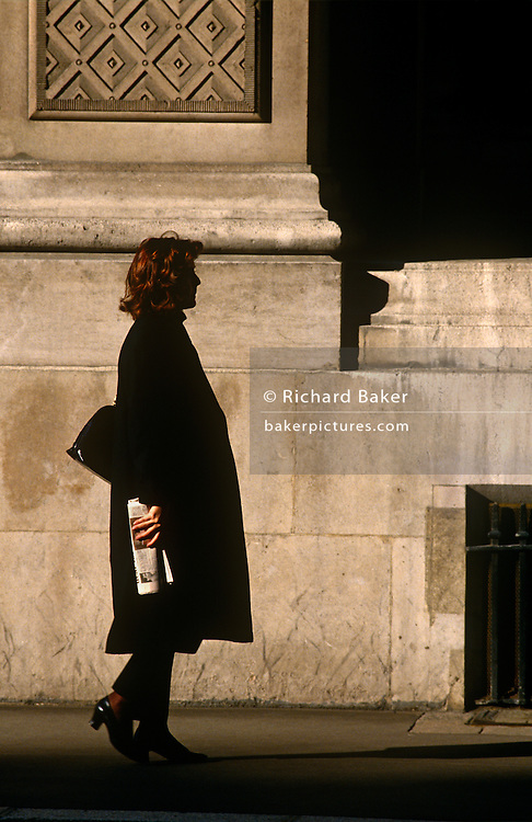 A lady walks along a City of London street holding a newspaper in her right hand.