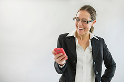 Businesswoman in black suit with smart phone, smiling