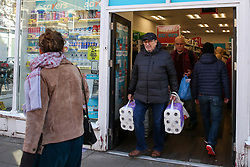© Licensed to London News Pictures. 16/03/2020. London, UK. A shopper leaves Savers store in north London with packs of toilet rolls. 35 coronavirus victims have died and 1,372 cases have tested positive of the virus in the UK. Photo credit: Dinendra Haria/LNP