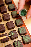 """Xocolatl Chocolate, where owner David Briggs preparing the """"Fresh Mint"""" chocolate which consists of mint infused ganache and is then carefully painted with holly green luster dust"""