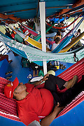A man takes nap in a hammock on a riverboat in Manacapuru, Brazil. Riverboats ply the network of rivers that drain the vast Amazon basin which has very few roads. (From the book What I Eat: Around the World in 80 Diets.) MODEL RELEASED.