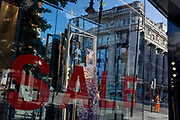 With a further 149 reported dying from Coronavirus in the last 24hrs, taking the UK death toll to 43,320, shoppers are distorted through the Sale window at the 'Zara' Oxford Street store which has recently re-opened foir business after easing of government lockdown rules. Union Jack flags hang alongside Thank You banners in support of NHS (National Health Service) key workers during the Covid pandemic, on 25th June 2020, in London, England.