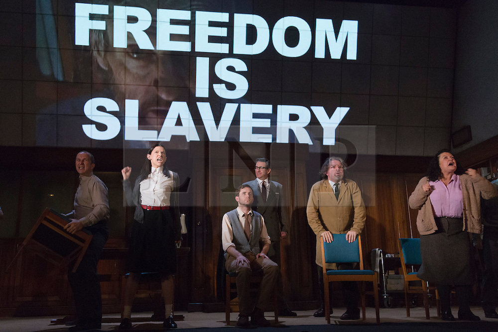"""© Licensed to London News Pictures. 08/05/2014. London, England. Pictured: L-R: Christopher Patrick Nolan as Martin, Hara Yannas as Julia, Sam Crane as Winston, Tim Dutton as O'Brien, Stephen Fewell as Charrington and Mandi Symonds as Mrs Parsons during the Two Minutes Hate. The Play """"1984"""" by George Orwell transfers to the Playhouse Theatre until 19 July 2014. A new adaptation for the stage by Robert Icke and Duncan MacMillan. With Sam Crane as Winston Smith. Photo credit: Bettina Strenske/LNP"""