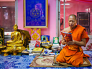 """29 MARCH 2017 - BANG KRUAI, NONTHABURI, THAILAND:  A Buddhist monk leads a prayer during a """"Resurrection Ceremony"""" at Wat Ta Kien (also spelled Wat Tahkian), a Buddhist temple in the suburbs of Bangkok. People go to the temple to participate in a """"Resurrection Ceremony."""" Groups of people meet and pray with the temple's Buddhist monks. Then they lie in coffins, the monks pull a pink sheet over them, symbolizing their ritualistic death. The sheet is then pulled back, and people sit up in the coffin, symbolizing their ritualist rebirth. The ceremony is supposed to expunge bad karma and bad luck from a person's life and also get people used to the idea of the inevitability of death. Most times, one person lays in one coffin, but there is family sized coffin that can accommodate up to six people. The temple has been doing the resurrection ceremonies for about nine years.         PHOTO BY JACK KURTZ"""