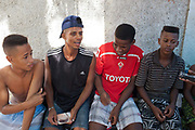 Three 3 young Brazilian men sitting on a bench in the street. Young independent barber shop hair stylist in the street for the young people guys of Vila Valquiere, West Zone Zona Oueste, Rio de Janeiro