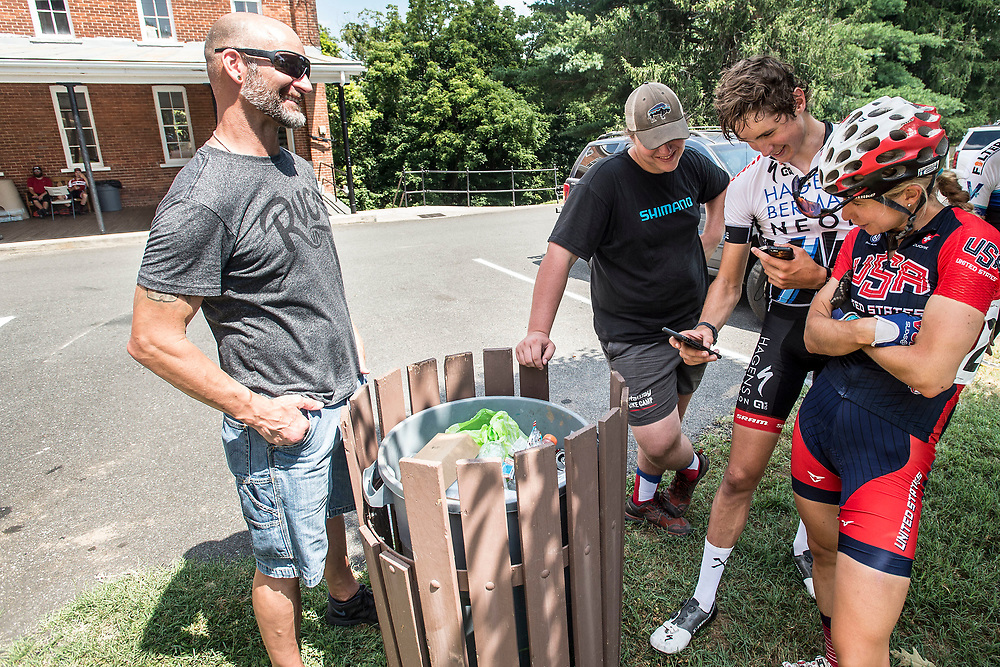 """CROZET, VA - JUL 16: Marcus, left, smiles as pro cyclists Andrea Dvorak, right, and Eddie Anderson, the winner of the Miller School race, look at Ben's efforts up a challenging local segment on the Strava app. """"402 watts, no way!"""" Dvorak, says in awe of Ben's performance up the climb in March. Ben finished 4th at Miller School, earning $70 and a visit to the podium. (Photo by Jay Westcott/The News & Advance)"""
