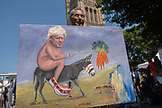 On the day Conservative MP Boris Johnson is announced as the new Prime Minister of the United Kingdom, political artist Kaya Mar with his latest artwork showing the new PM, naked riding a donkey to a cliff edge on the 23rd July 2019 in London in the United Kingdom.
