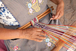 North America, Mexico, Oaxaca Province, Oaxaca, woman using backstrap loop to weave belt (lower torso)