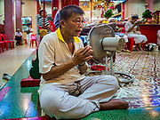 """22 AUGUST 2017 - BANGKOK, THAILAND: A man prays during a ceremony on the first day of Hungry Ghost Month at the Poh Teck Tung Shrine in Bangkok's Chinatown. The seventh lunar month (August - September) is when many Chinese believe Hell's gate will open to allow spirits to roam freely in the human world. Many households and temples hold prayer ceremonies throughout the month-long Hungry Ghost Festival (Phor Thor) to appease the spirits. During the festival, believers will also worship the Tai Su Yeah (King of Hades) in the form of paper effigies which will be """"sent back"""" to hell after the effigies are burnt.      PHOTO BY JACK KURTZ"""