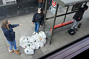 Two women shoppers stand over their purchases while waiting for the next bus on the Walworth Road in south London, on 29th April 2021, in London, England.