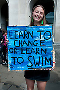 School Climate Strike, London, England, UK. A girl holds a blue painted placard saying Learn to change or learn to swim referencing rising water levels.