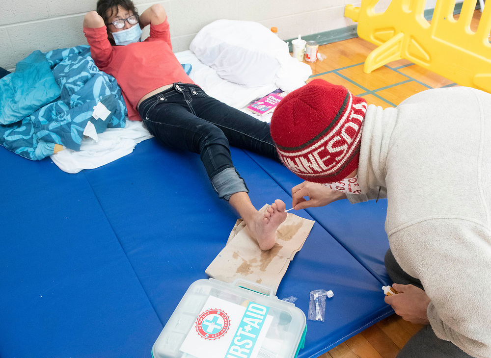 Austin, Texas Feb. 16, 2021: Deborah Michalewicz, who is homeless, is tended to by medical student Robin Daemmrich at a church-run emergency clinic in ater fleeing freezing cold and snow outside.  A historic snow of 8 inches coupled with bitterly-cold temperatures have forced hundreds living outside to seek shelter.