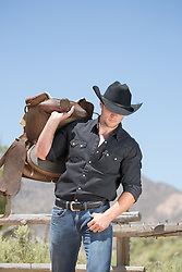 cowboy with a saddle over his shoulder