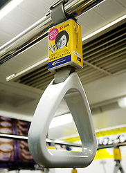 Detail of handle on Tokyo subway with advertising