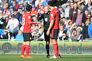 The referee Martin Atkinson has a few strong words with Cardiff City's Kim Bo-Kyung (l) during the Barclays Premier league, Cardiff city v Fulham at the Cardiff city Stadium in Cardiff , South Wales on Sat 8th March 2014. pic by Jeff Thomas/Andrew Orchard sports photography