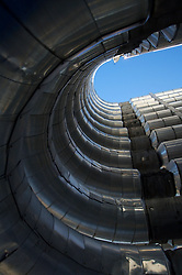 Upward view of blue sky from between stacks of curved pipes at a petrochemical plant (Sunoco).