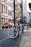 A bike rests against a metal pole on a street in New Orleans, Louisiana