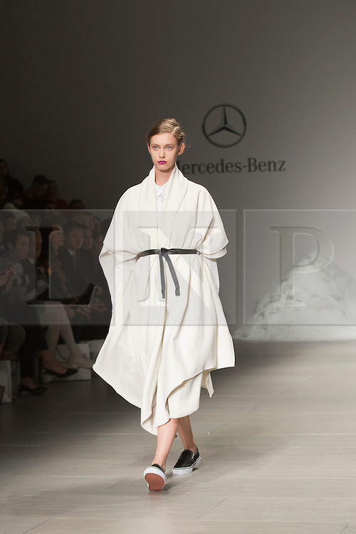 © Licensed to London News Pictures. 18 February 2014, London, England, UK. A model walks the runway at the Mercedes-Benz sponsored SIMONGAO show during London Fashion Week AW14 at the BFC Courtyard Show Space/Somerset House. Photo credit: Bettina Strenske/LNP
