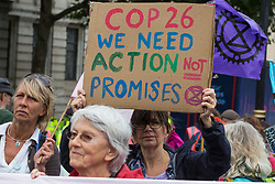 An environmental activist from Extinction Rebellion holds a sign calling for action at COP26 during the first day of Impossible Rebellion protests on 23rd August 2021 in London, United Kingdom. Extinction Rebellion are calling on the UK government to cease all new fossil fuel investment with immediate effect. (photo by Mark Kerrison/In Pictures via Getty Images)