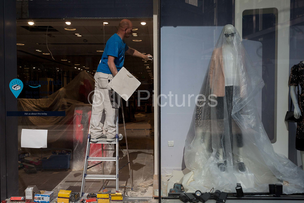 Ten weeks after the UK went into Coronavirus pandemic lockdown, the Office for National Statistics reveal that the total death toll has passed 50,000 covid-19 victims, clothing mannequins in the shop window of a retailer undergoing extensive refurbishment, are covered in a protective layer of plastic, in the City of London, the capitals financial district, on 2nd June 2020, in London, England. The retail industry has taken advantage of quiet roads during lockdown, as an opportunity to have repairs and refurbs caried out in their premises.