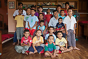 Orphan Nepalese boys gather around 'Auntie and Uncle' in the living room of their care home in Kathmandu, Nepal.  The care home is run by the Friends of Needy Children organization.  It provides a loving home for boys and girls who are orphaned or abandoned.  Abject poverty, domestic violence and armed conflict have caused many Nepalese children orphaned and homeless.  This care home for boys is called 'J house' and is at maximum capacity with 18 children of varying ages.