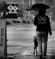 A woman with an umbrella walks her dog in downtown Bremerton.  A series of pedestrian signs repeat in the background and are repeated on the woman's back.