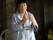 Namgay Pedon hand spinning wild silk using a drop spindle in Rangjung village, Eastern Bhutan. This area is famous for fine raw silk or bura textiles woven using natural dyes and a traditional back-strap loom.