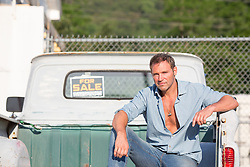 portrait of a handsome middle aged man outdoors sitting on a pickup truck