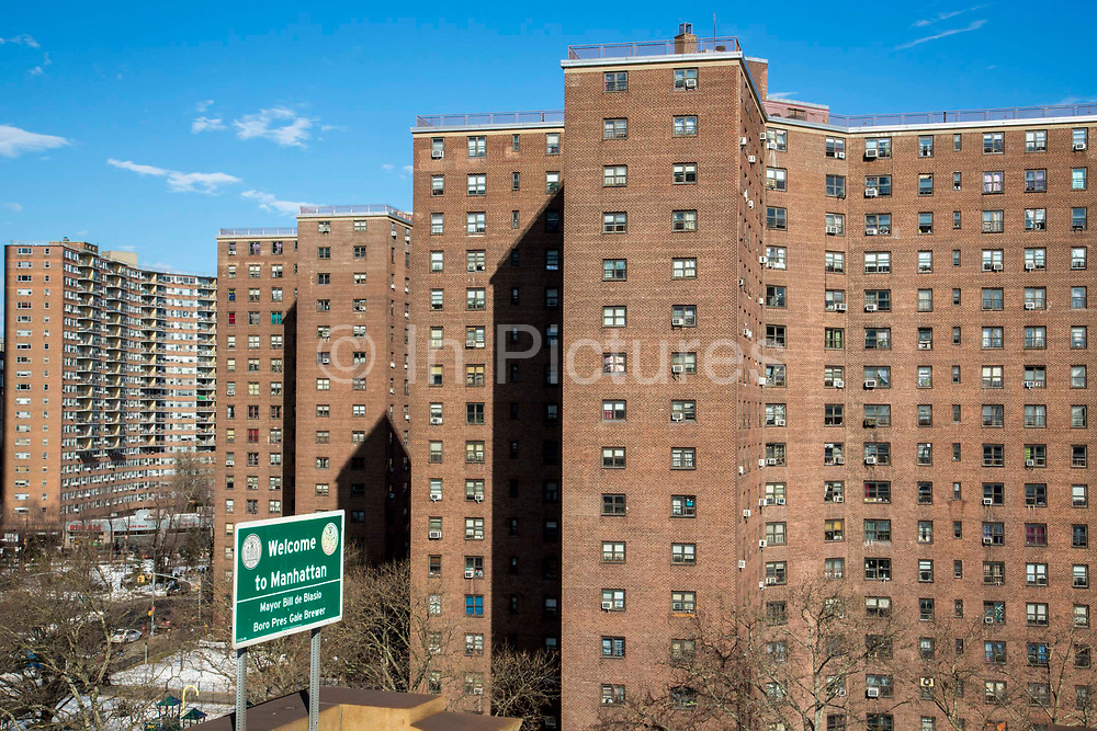 'Welcome to Manhattan' sign at the end of the Brooklyn Bridge in front of the red brick apartment blocks of The Governor Alfred E. Smith Houses, a public housing development built by the New York City Housing Authority in the Two Bridges neighbourhood of the Lower East Side of Manhattan.  There are 12 buildings in this complex, each 17 stories tall and houses approximately 5,739 people.
