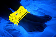 Feet on veil wrapped with a glowing yellow chain.Black light