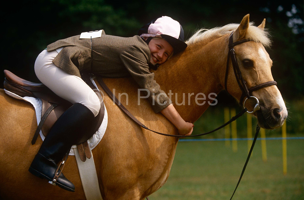 """A young girl hugs her beloved pony at a gymkhana meeting in Cheltenham, Gloucestershire, England. Gymkhana is an Indian Raj term which originally referred to a place where sporting events took place and referred to any of various meets at which contests were held to test the skill of the competitors. In the United Kingdom and east coast of the United States, the term gymkhana now almost always refers to an equestrian event for riders on horses, often with the emphasis on children's participation (such as those organised here by the Pony Club). Gymkhana classes include timed speed events such as barrel racing, keyhole, keg race (also known as """"down and back""""), flag race, and pole bending."""